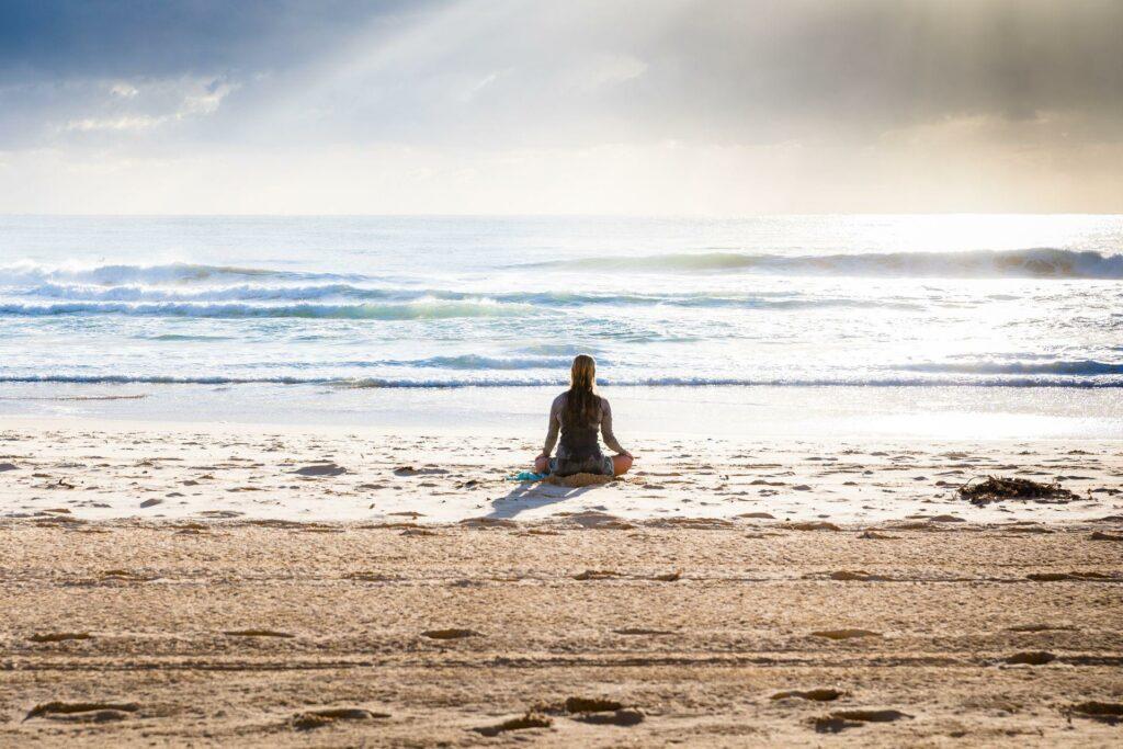 En kvinde sidder og laver meditation og mindfulness på en strand